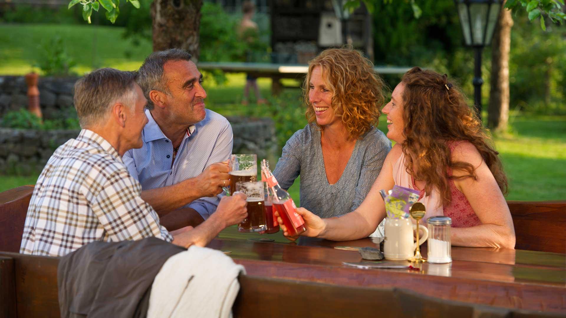 Freunde genießen den Sommer bei einem kühlen Getränke im Biergarten
